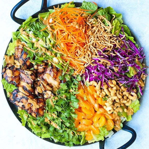 Bright rainbow colored salad with grilled chicken on a dark plate set on a white countertop is just one of 35 easy lunch ideas and recipes.