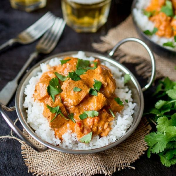 Silver pan on a burlap coaster with rice, chicken, and parsley highlight these easy crock pot recipes.