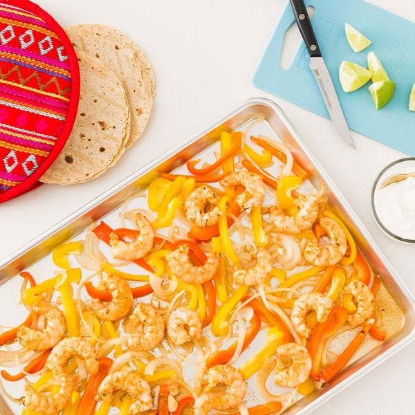 One of many quick keto dinner recipes shown on a silver cooking sheet with yellow and orange bell peppers, onions, and shrimp.