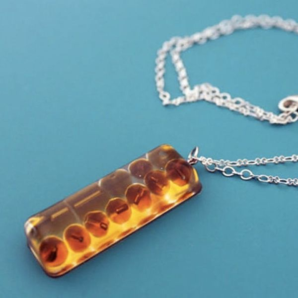 Close-up view of amber resin jewelry pendant on a silver chain