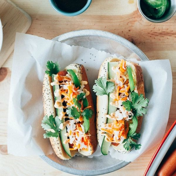 A pair of colorful Bánh Mì Hot Dogs with dandelion and jalapeños