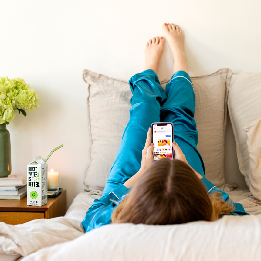 woman in bed scrolling on phone looking at memes
