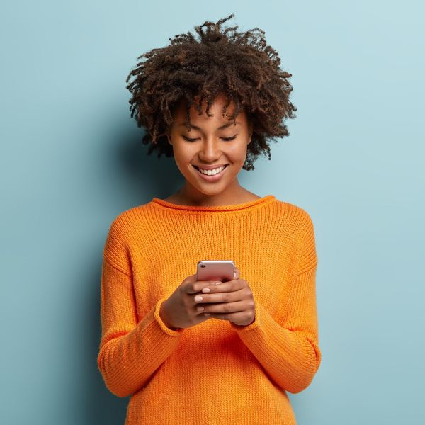woman in orange sweater scrolling on smartphone