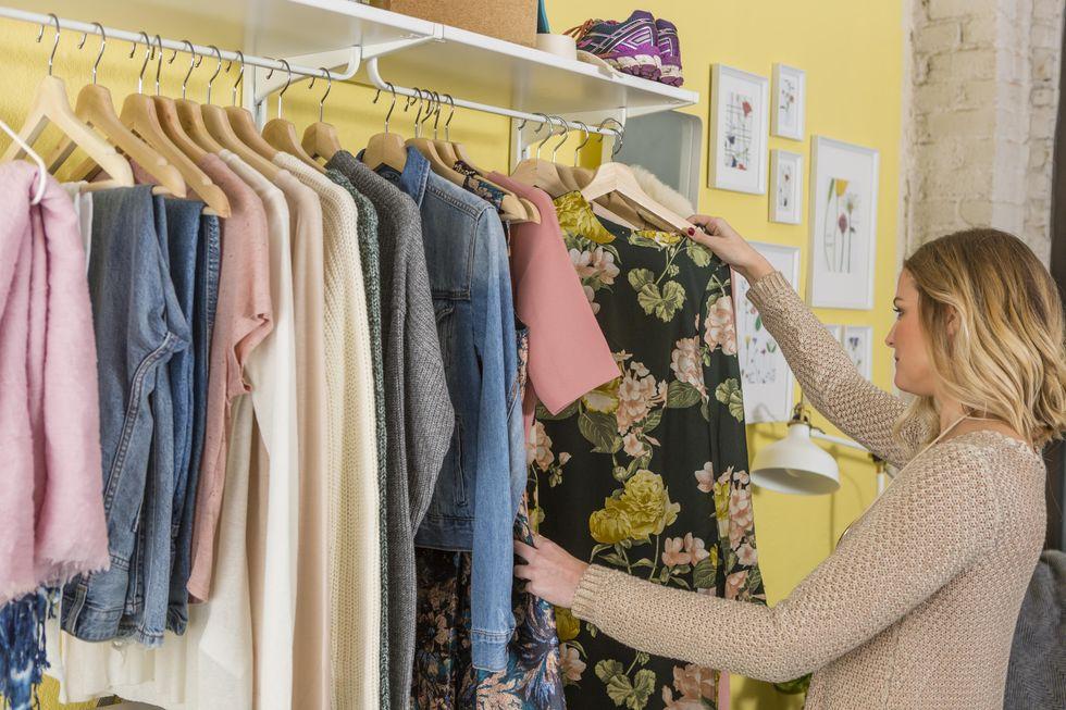 Woman sorting through closet wardrobe clothes