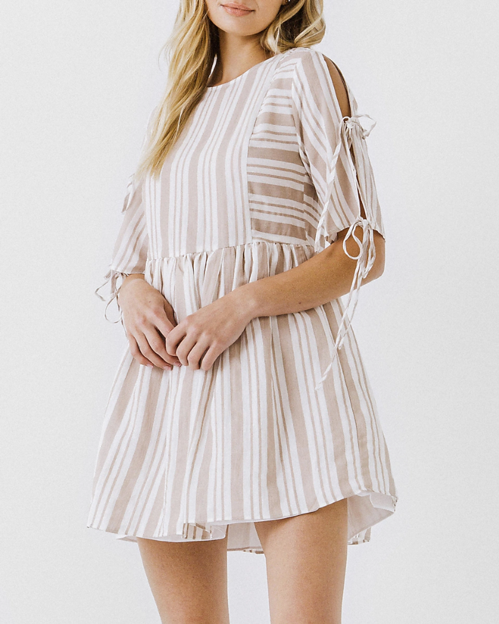 model wears tan and white striped mini dress with tie sleeves