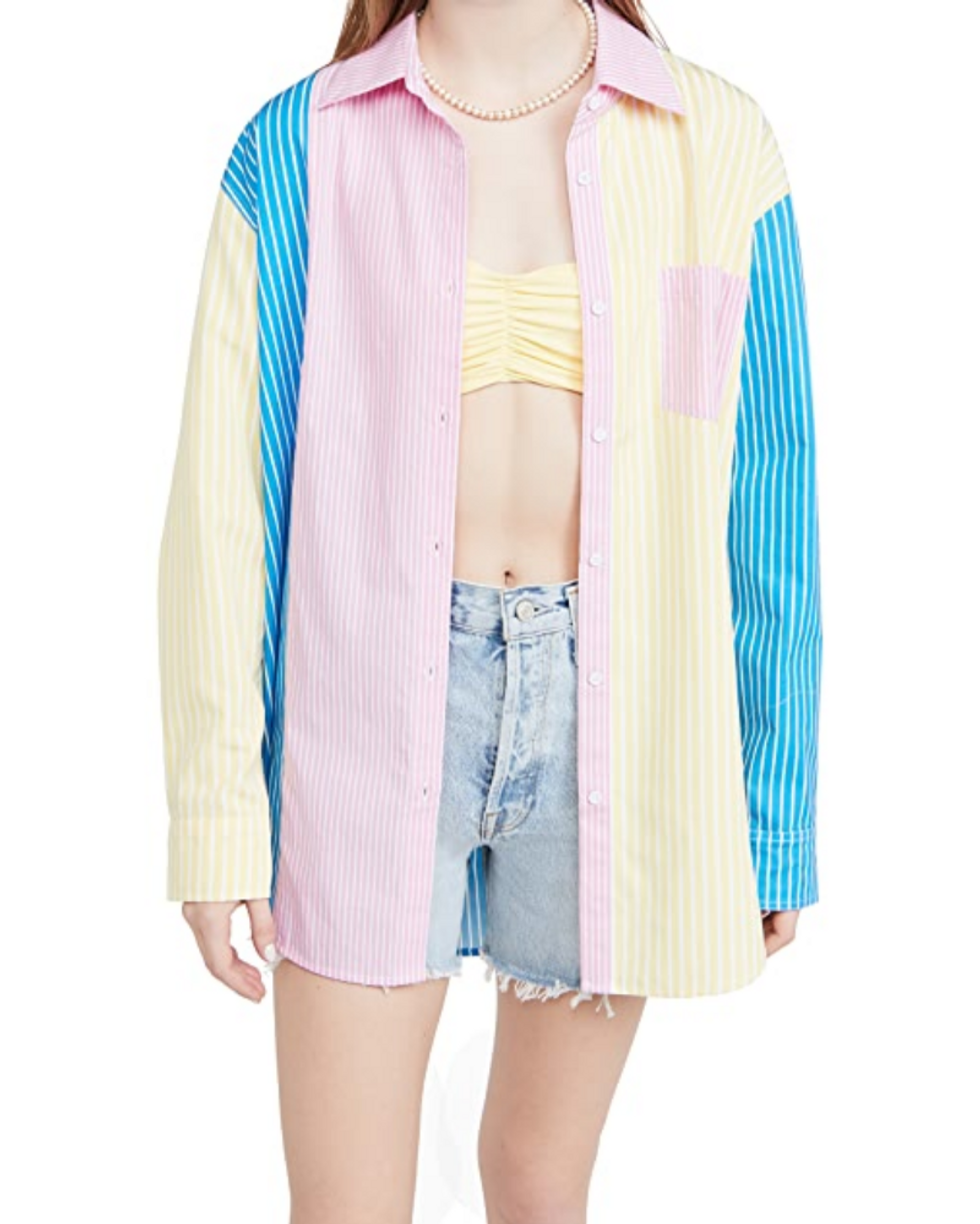 model wears yellow, blue, and pink shirtdress over bikini top and denim shorts