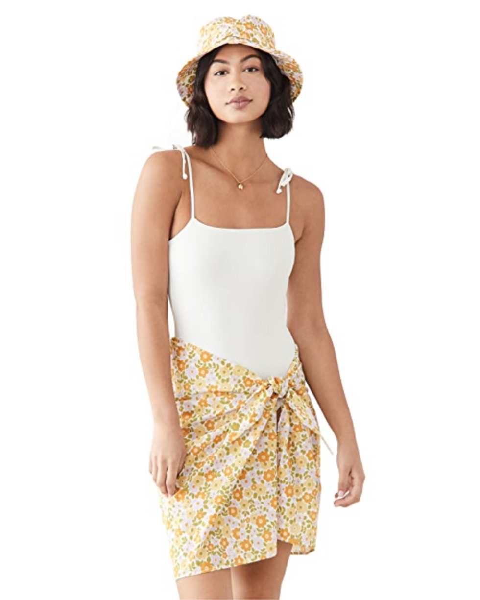 model wears orange, yellow, and green skirt set with a white bathing suit and bucket hat