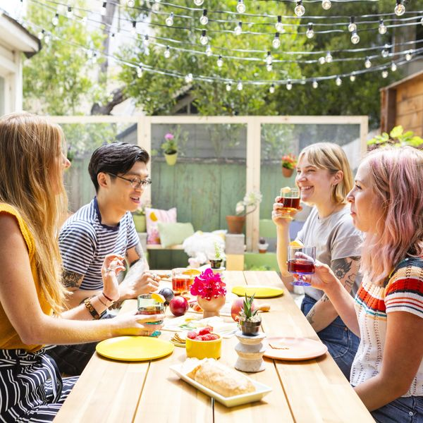 friends sitting around a table for outdoor dining with rainbow decor