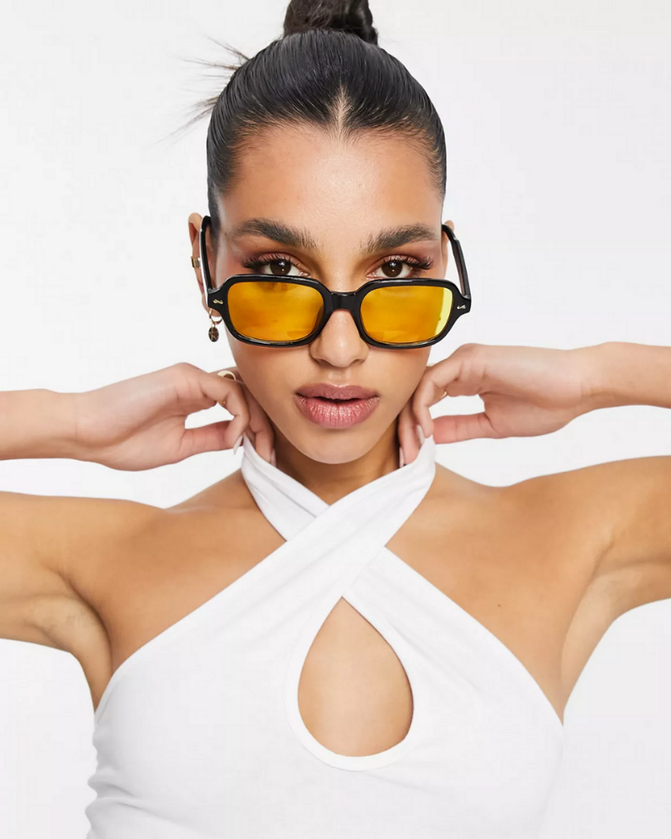 model wears yellow and black glasses with white top