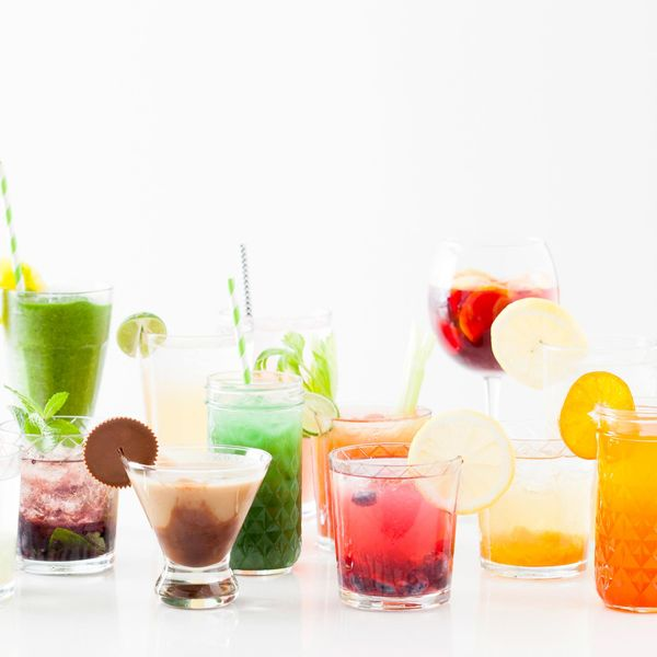 A rainbow display of various cocktail recipes with fruit and chocolate on a white counter with a white background