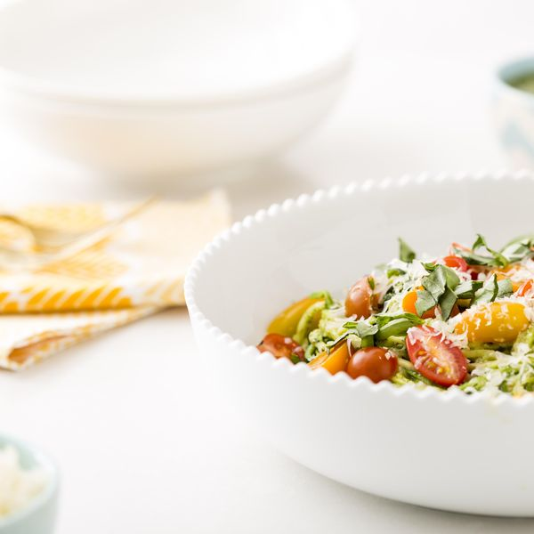 White bowl of zoodles on a white table features a bright salad with cherry tomatoes is one of our 15 easy healthy lunch ideas to avoid the afternoon crash.